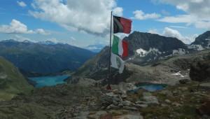 Le bandiere del Rifugio Perucca Vuillermoz tra il lago di Balanselmo e la diga di Cignana – Foto di Gian Mario Navillod.